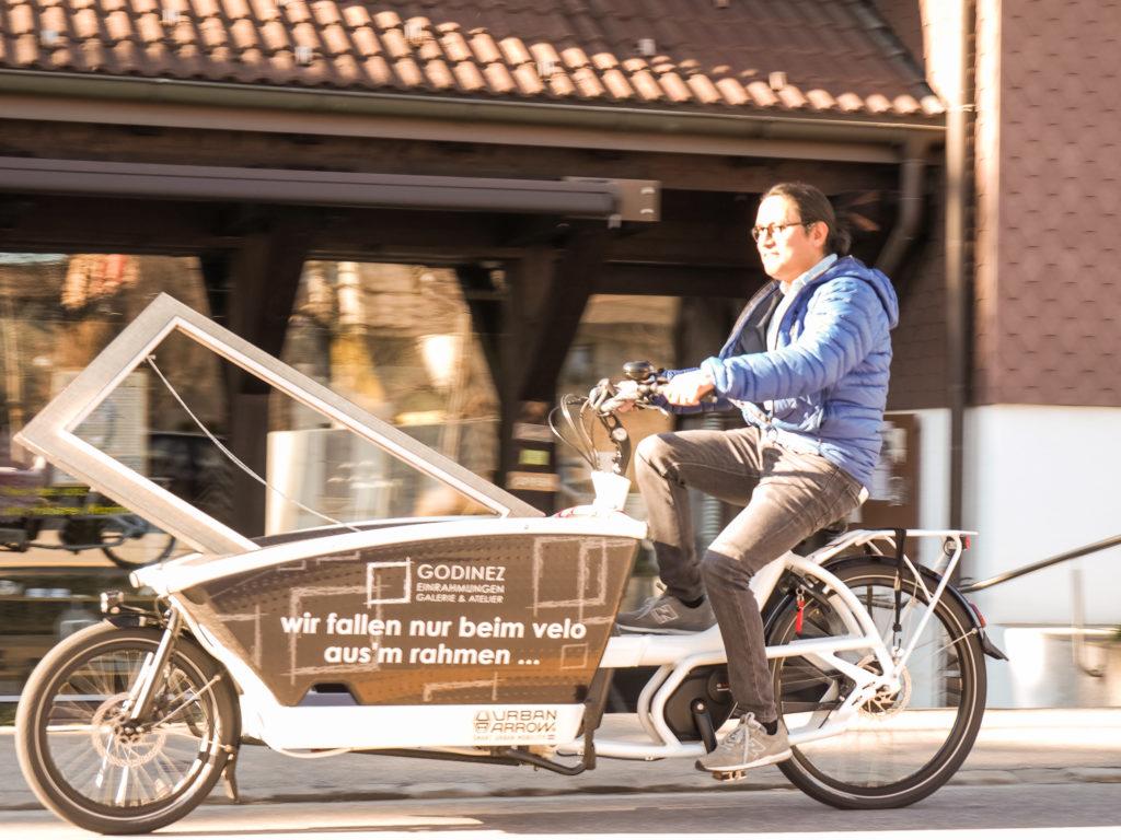Mann liefert Bilderrahmen mit Lastenrad